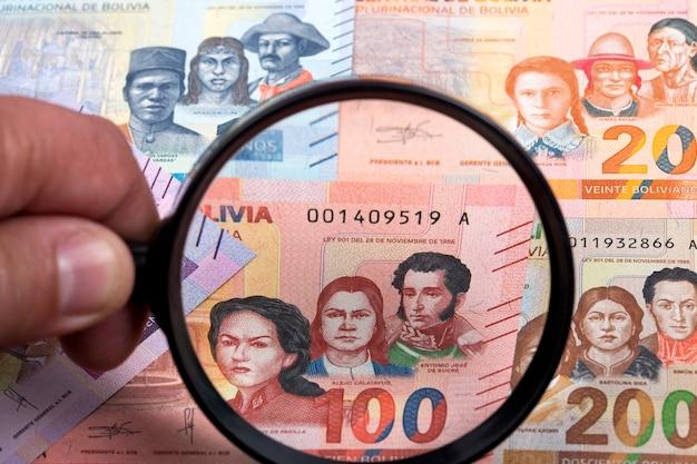 Boliviaans geld in een vergrootglas een bedrijfsachtergrond