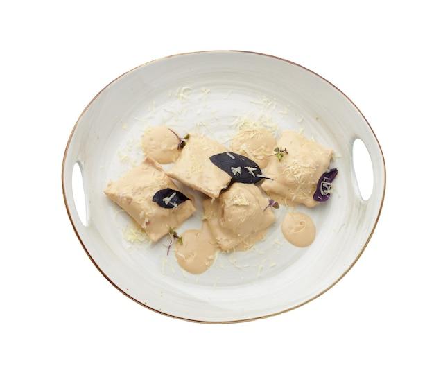 Bollen of vareniki met champignonsaus op wit wordt geïsoleerd