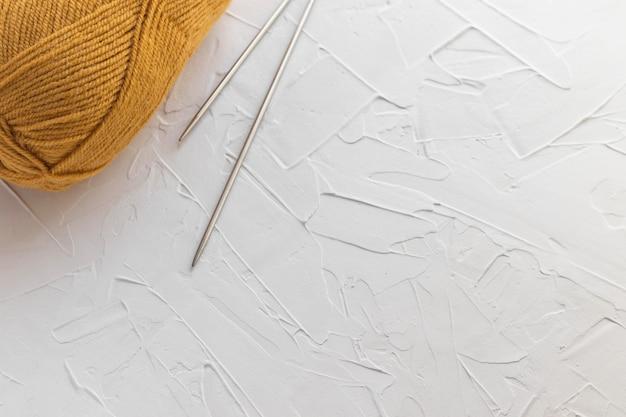 Bolletje mosterdwol en paar metalen gebreide naalden. oranje draden om te breien.