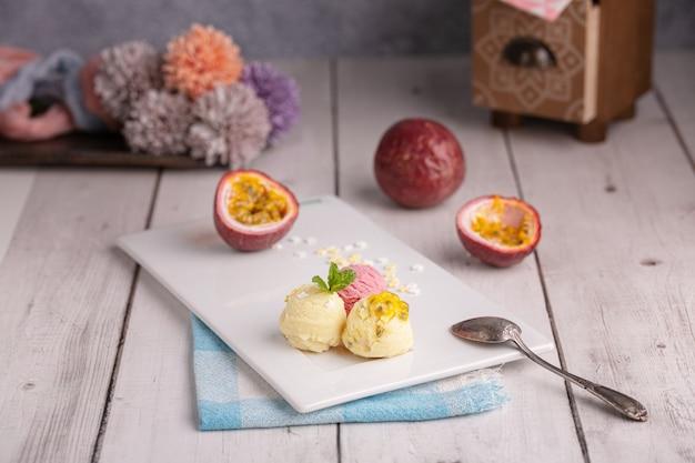 Bolletjes passie-, vanille- en aardbeienijs op een witte plaat op een houten tafel
