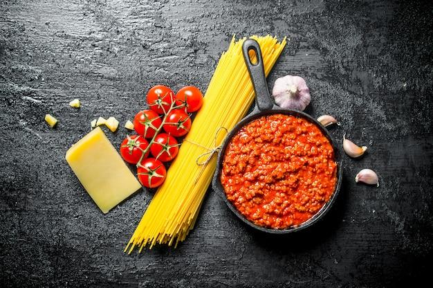Bolognesesaus in pan met droge pasta, kruiden en parmezaanse kaas