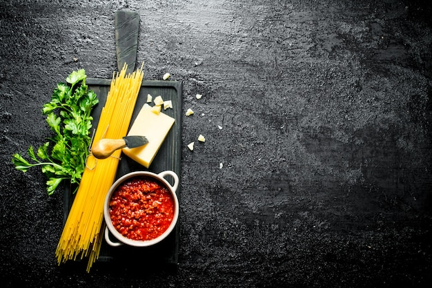 Bolognesesaus met droge pasta en kruiden. op zwarte rustieke achtergrond