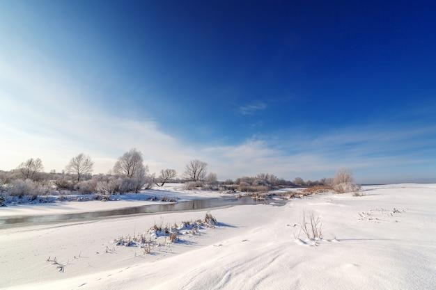 Bomen bedekt met rijm aan de oevers van een bevroren rivier.