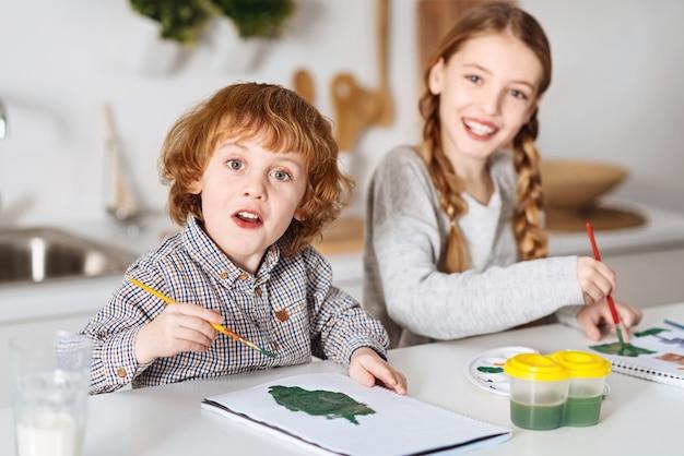 Bomen en struiken. enthousiaste creatieve lieve kinderen die zich vermaken en genieten van het schilderproces terwijl ze aan tafel in de keuken zitten