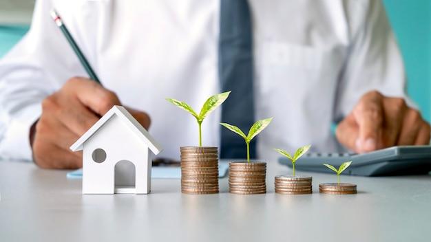 Bomen groeien op een stapel munten, hypotheekconcept, hypotheek, onroerend goed en hypothecaire leningen
