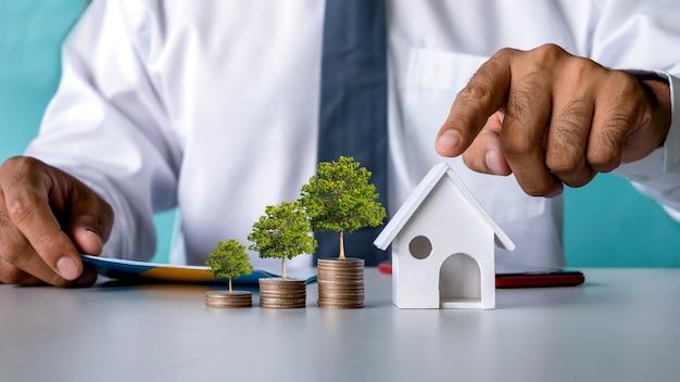 Bomen groeien op stapels munten en woningmodellen simuleren hypotheek- en vastgoedleningen.