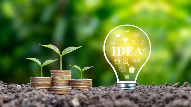 Bomen groeien van munten en spaarlampen met het label idea, groeiende financiële ideeën en hoe u zakelijke ideeën kunt vinden die voor u werken.