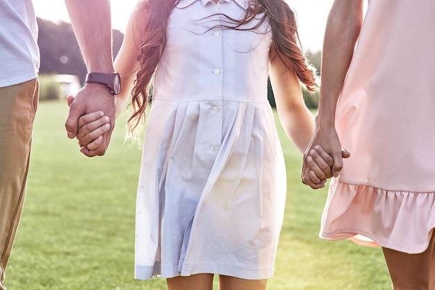 Bonding familie van drie hand in hand lopen op grasveld d