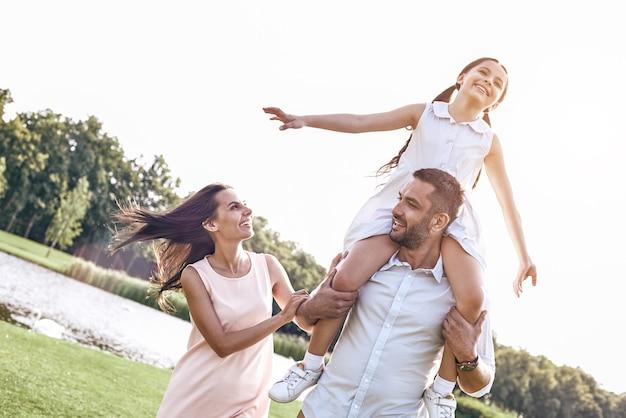 Bonding familie van drie wandelen op grasveld meisje zittend op