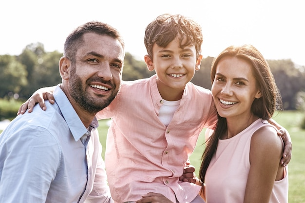Bonding familie van drie wandelen op grasveld zoon knuffelen par