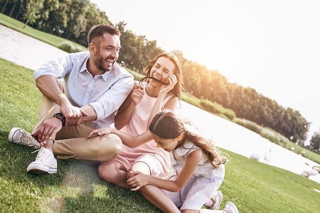 Bonding familie van drie zittend op grasveld met plezier laug