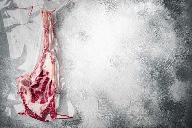 Bone tomahawk steak in vacuüm commerciële verpakkingsset, op grijze stenen achtergrond, bovenaanzicht plat gelegd, met kopieerruimte voor tekst