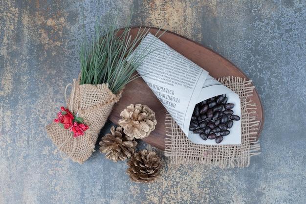 Bonen in krant met dennenappels op houten bord.