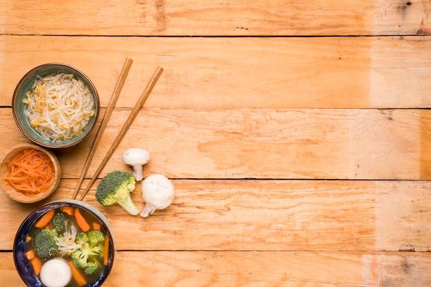 Bonen ontspruiten; wortel; en vis bal soep met stokjes op houten tafel