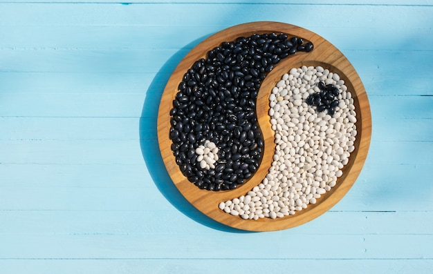 Bonen op een bord yin en yang gezond voedsel eiwit bovenaanzicht op een houten achtergrond