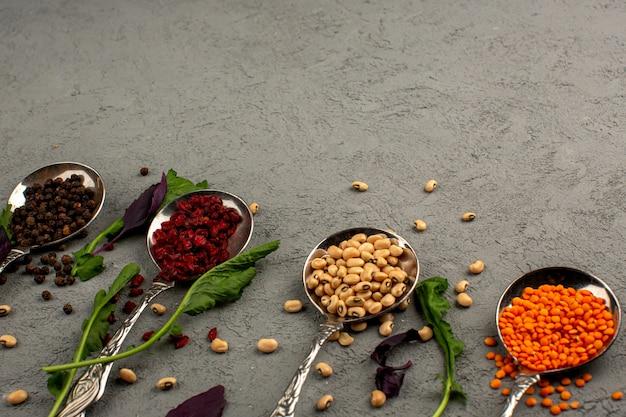Bonen rauw gekleurd samen met gedroogde hete pittige kruiden op een grijze vloer
