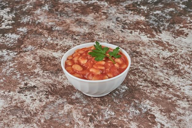 Bonen soep in tomatensaus in een keramische beker.