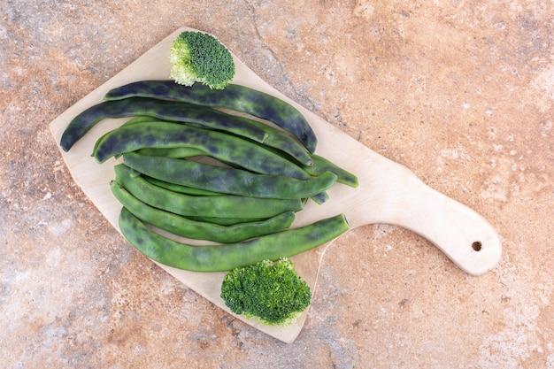 Bonenpulsbundel en een stuk broccoli op een marmeren oppervlak