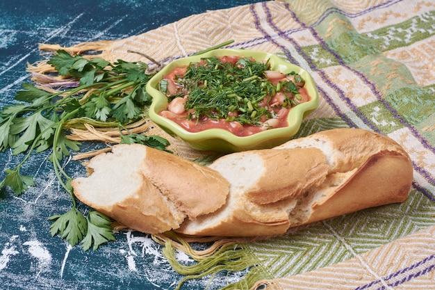 Bonensoep in tomatensaus met kruiden en brood.