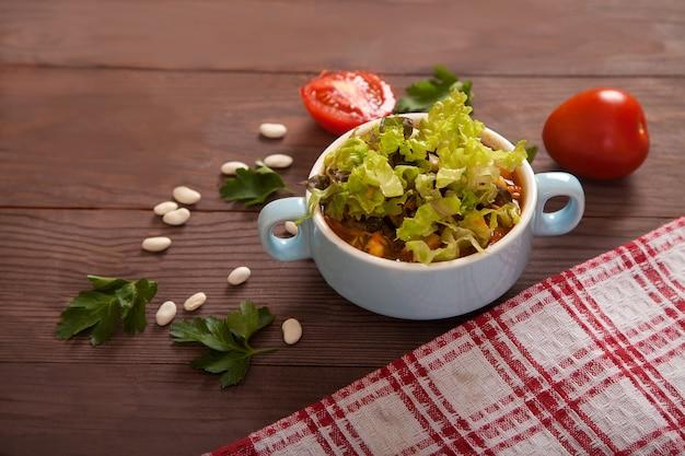 Bonensoep, tomaten, bonen, peterselie en een geruit linnen servet op een houten tafel.