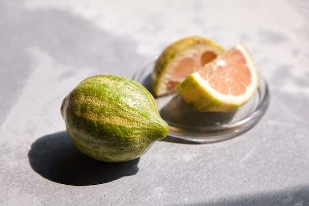 Bonte eureka-citroen met gestreepte korst in glazen schotel op betonnen tafel