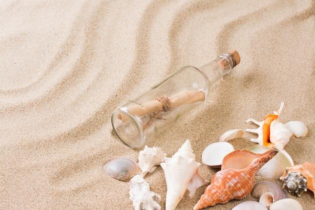 Boodschap in fles op het strand. de zomerachtergrond met heet zand
