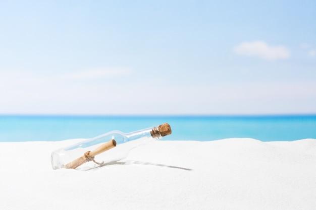 Boodschap in fles op strand met wit zand, in tropische zee