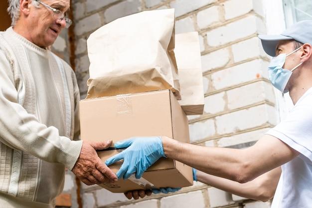 Boodschappen doen bij het boodschappen doen voor oudere senior die aan de deur staat.