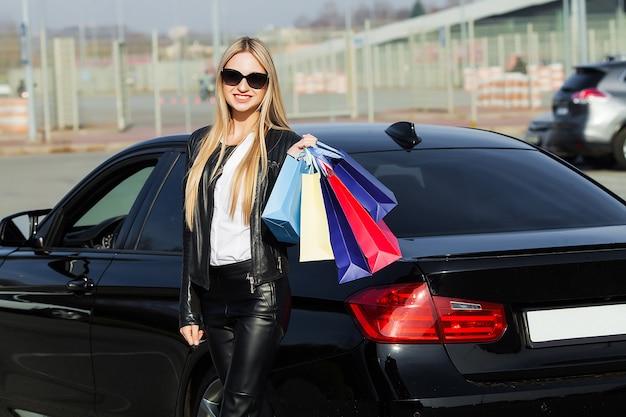 Boodschappen doen. de vrouwenholding kleurde zakken dichtbij haar auto in zwarte vrijdagvakantie