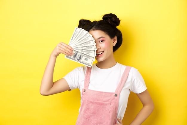 Boodschappen doen. mooi aziatisch vrouwelijk model met glamourmake-up, bedek de helft van het gezicht met geld dollarbiljetten, sensueel glimlachend in de camera, geel.