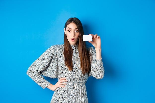 Boodschappen doen. opgewonden meisje toont haar plastic creditcard en kijkt naar kortingen, zeg wow verbaasd, staande op blauw.