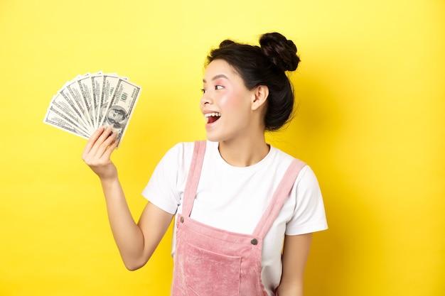 Boodschappen doen. rijk en stijlvol aziatisch vrouwelijk model dat geld toont, dollarbiljetten bekijkt met een blij gezicht, staande op geel
