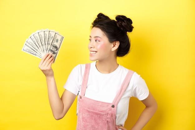 Boodschappen doen. rijk en stijlvol aziatisch vrouwelijk model dat geld toont, dollarbiljetten met een tevreden glimlach bekijkt, die zich op geel bevindt.