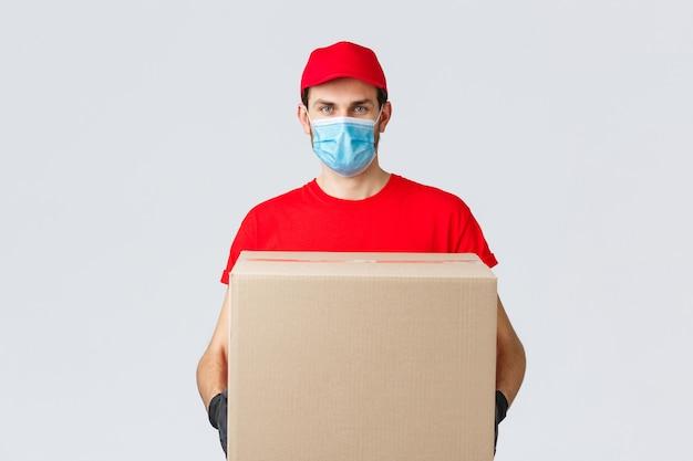 Boodschappen en pakketten bezorgen, covid-19, quarantaine en winkelconcept. ernstige koerier in rood uniform, handschoenen en beschermend gezichtsmasker, bezorg de pakketdoos aan het huis van de klant tijdens het coronavirus