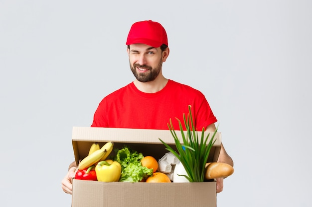 Boodschappen en pakketten bezorgen, covid-19, quarantaine en winkelconcept. knappe glimlachende koerier in rood uniform, geef een brutale knipoog als het leveren van voedseldoos, online bestelling aan het huis van de klant.