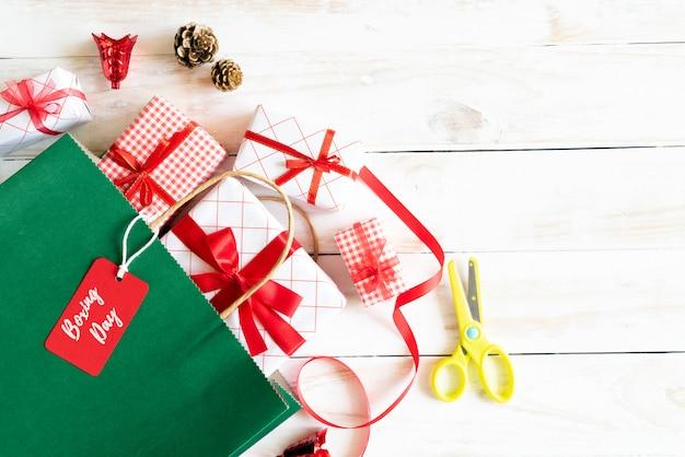 Boodschappentas en geschenkdoos op een houten witte achtergrond. tweede kerstdag concept.