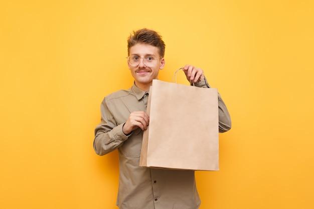 Boodschappentas in papieren zak geïsoleerd op geel, in de camera kijken en glimlachen