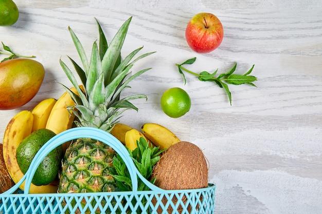 Boodschappentas met biologische exotische vruchten op witte achtergrond.