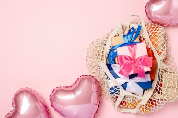 Boodschappentas met cadeau en hartvormige luchtballon op een roze oppervlak. geschenkenconcept voor familie, geliefden, kerstmis, valentijnsdag. . plat lag, bovenaanzicht