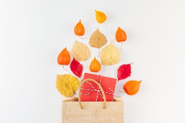 Boodschappentas met gedroogde oranje bloemen en herfstbladeren