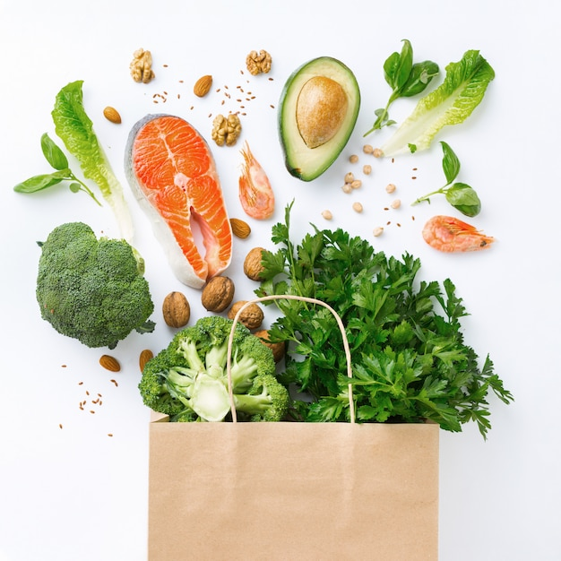 Boodschappentas met gezond voedsel op witte achtergrond met kopie ruimte bovenaanzicht