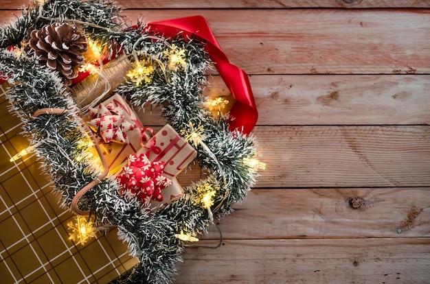 Boodschappentas met kerstcadeautjes en ornamenten op houten achtergrond verlicht door gele lichten