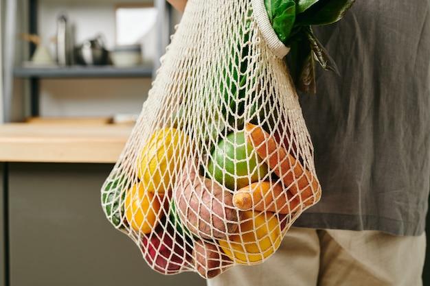 Boodschappentas met rauwe groenten en fruit vastgehouden door jonge vrouw in vrijetijdskleding