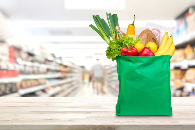 Boodschappentas met voedsel en boodschappen op de tafel in de supermarkt