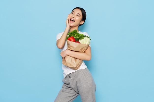 Boodschappentas winkelen gezond voedsel groenten vrolijke aziatische vrouw blauw fonds