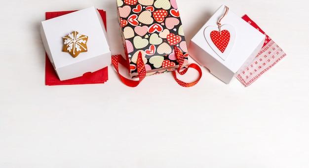 Boodschappentas, witte doos en rood hart van valentijnsdag op witte muur