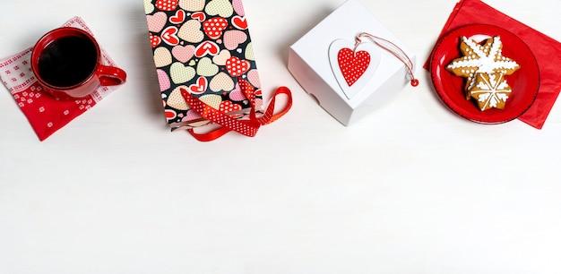 Boodschappentas, witte doos, kopje koffie, koekje en rood hart van valentijnsdag op witte muur