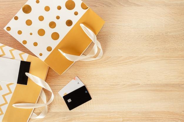Boodschappentassen en creditcards op houten achtergrond. ruimte kopiëren, bovenaanzicht