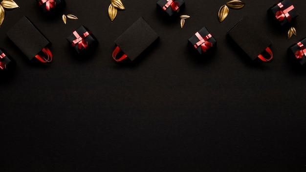 Boodschappentassen en gouden bladeren op zwarte achtergrond