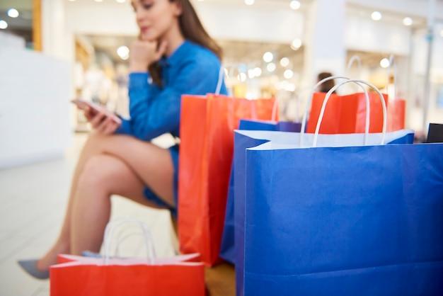 Boodschappentassen en vrouw met mobiele telefoon